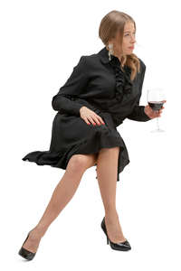 woman in a black dress drinking wine