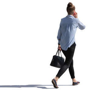 backlit woman walking and talking on the phone