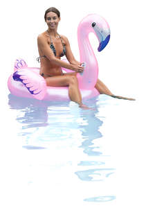 woman floating on a pink flamingo in a pool
