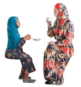 muslim mother and daughter sitting in a cafe and talking