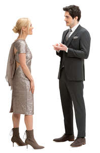 man and woman in party clothes standing and talking