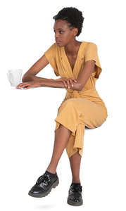 black woman in a yellow jumpsuit sitting in a cafe