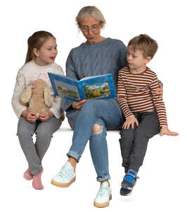 grandmother sitting and reading a book to her grandchildren