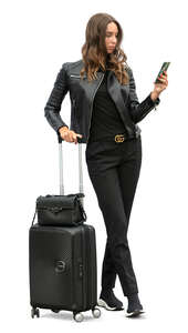 woman with suitcase standing and checking her phone