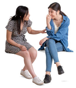 two young asian women sitting and talking