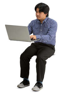 asian man sittinf behind a desk with laptop