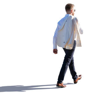 backlit man walking with a jacket over his shoulder
