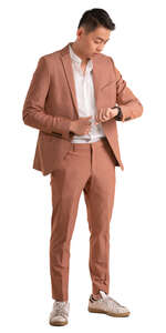 asian man in pink suit standing and looking at his watch