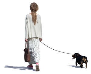 woman in a long white dress walking a dog
