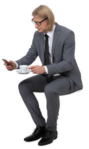 man in a suit drinking coffee in a cafe