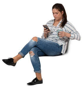 woman with a coffee mug sitting and texting