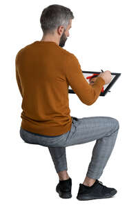 man sitting and drawing on computer