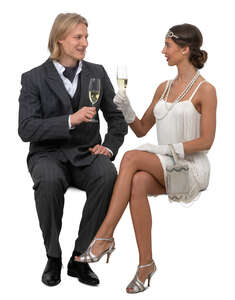man and woman in fancy clothes sitting and drinking champagne