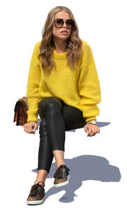 woman in a yellow knit sweater sitting