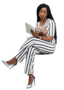 woman in a striped jumpsuit reading a magazine