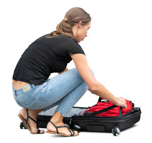 woman squatting and packing her suitcase