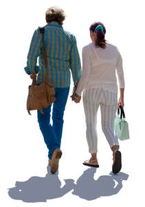 elderly backlit couple walking hand in hand