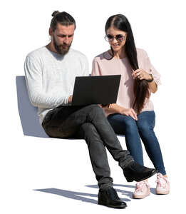 man and woman sitting and looking at a laptop