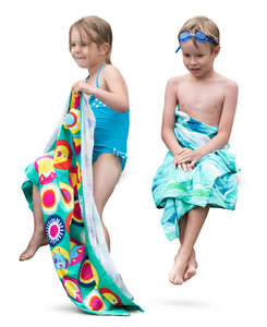 two kids with towels sitting after swimming