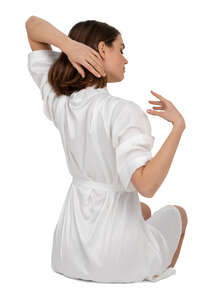 woman in a white bathrobe sitting