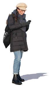 woman in a winter overcoat standing and texting