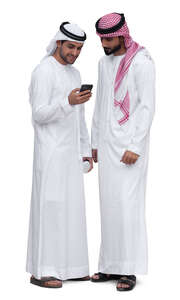 two emirati men standing and looking at a phone