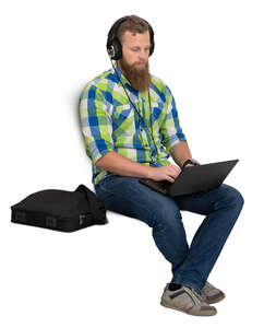 man with headphones sitting and working with laptop