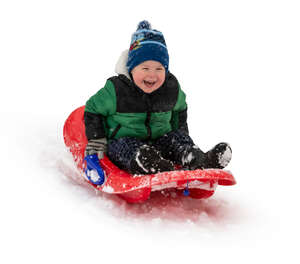 happy little boy sledging down the hill