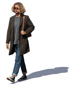 man with curly hair and light overcoat walking