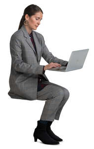woman in a grey costume sitting and working with laptop