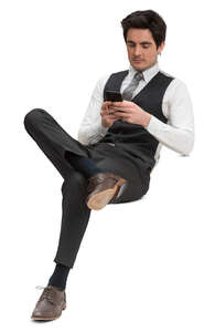 man in a formal suit vest sitting and texting