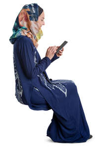 muslim woman sitting and looking at her phone
