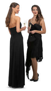 two women in black evening dresses at a formal event standing and talking
