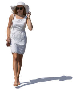 woman in a white summer dress and hat walking