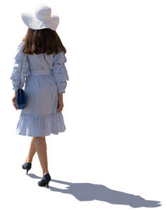 backlit image of a woman in summer dress walking