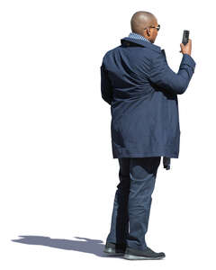 black man standing and taking a picture with his phone