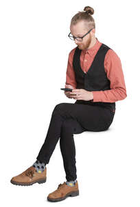 trendy young man sitting and looking at his phone