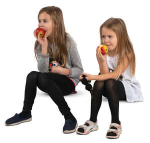 two girls sitting and eating apples