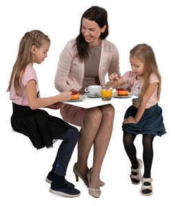 mother with two kids eating cake at a cafe