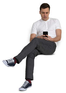 man sitting casually and checking his phone