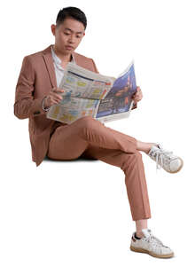 asian man in a pink suit sitting and reading a newspaper