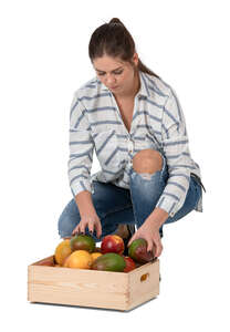 woman squatting and putting fruits in a box