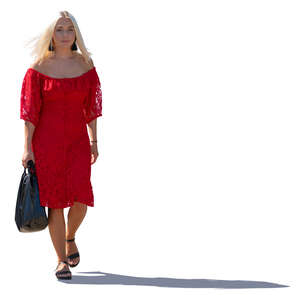 backlit woman in a red dress walking