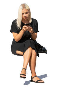 woman in a black summer dress sitting and texting