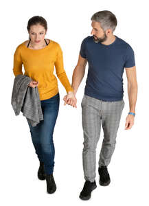 man and woman walking hand in hand seen from above