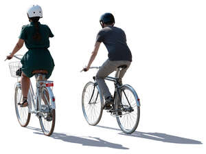 backlit man and woman cycling side by side