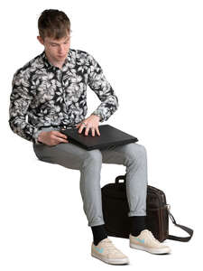 young man sitting and opening a laptop