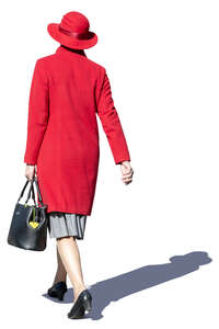 middle aged woman in a red hat and overcoat walking