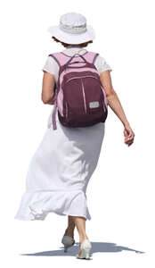 woman in a white dress carrying a backpack walking