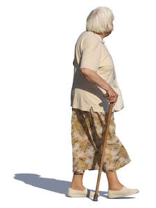 elderly woman with a walking stick walking on a summer day